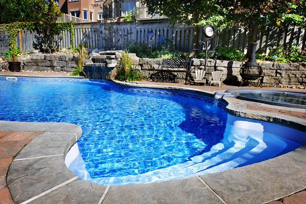 pool showcasing its nice liner and steps opening up to the beautiful yard